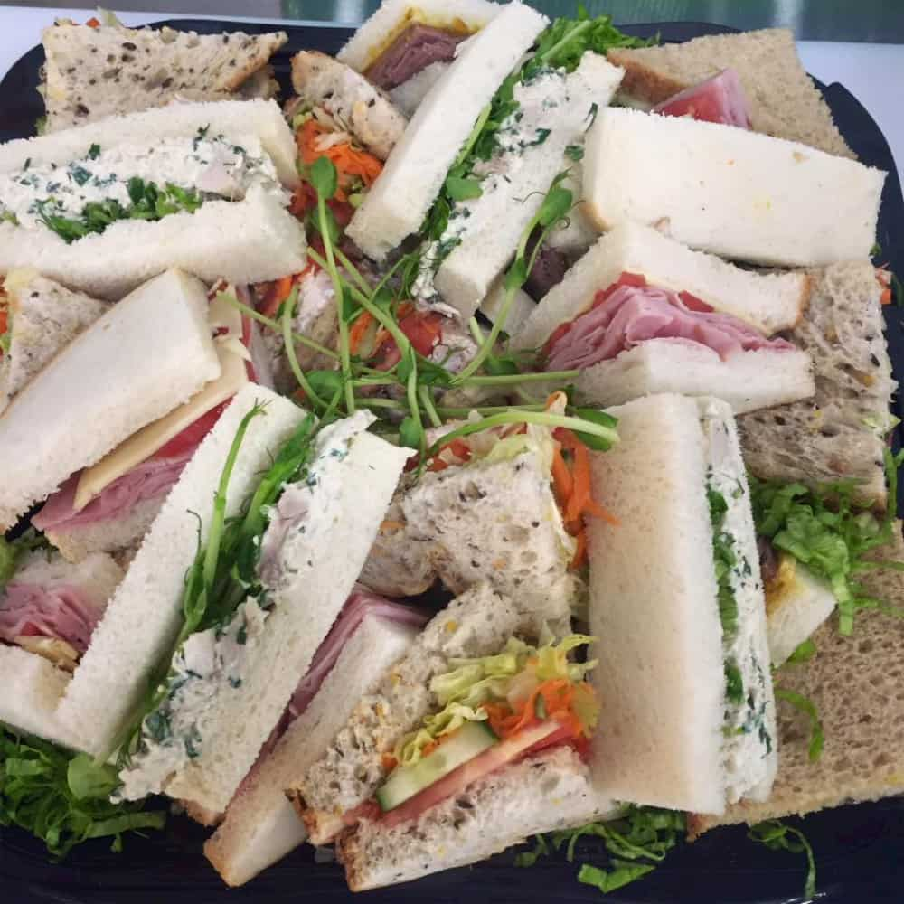 This is a selection of gourmet sandwiches with ham, salad and mixed cheeses.