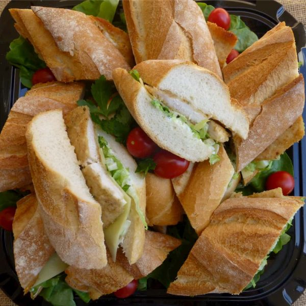 You are looking at a plate of fresh cut baguettes with chicken., salad and cheese.