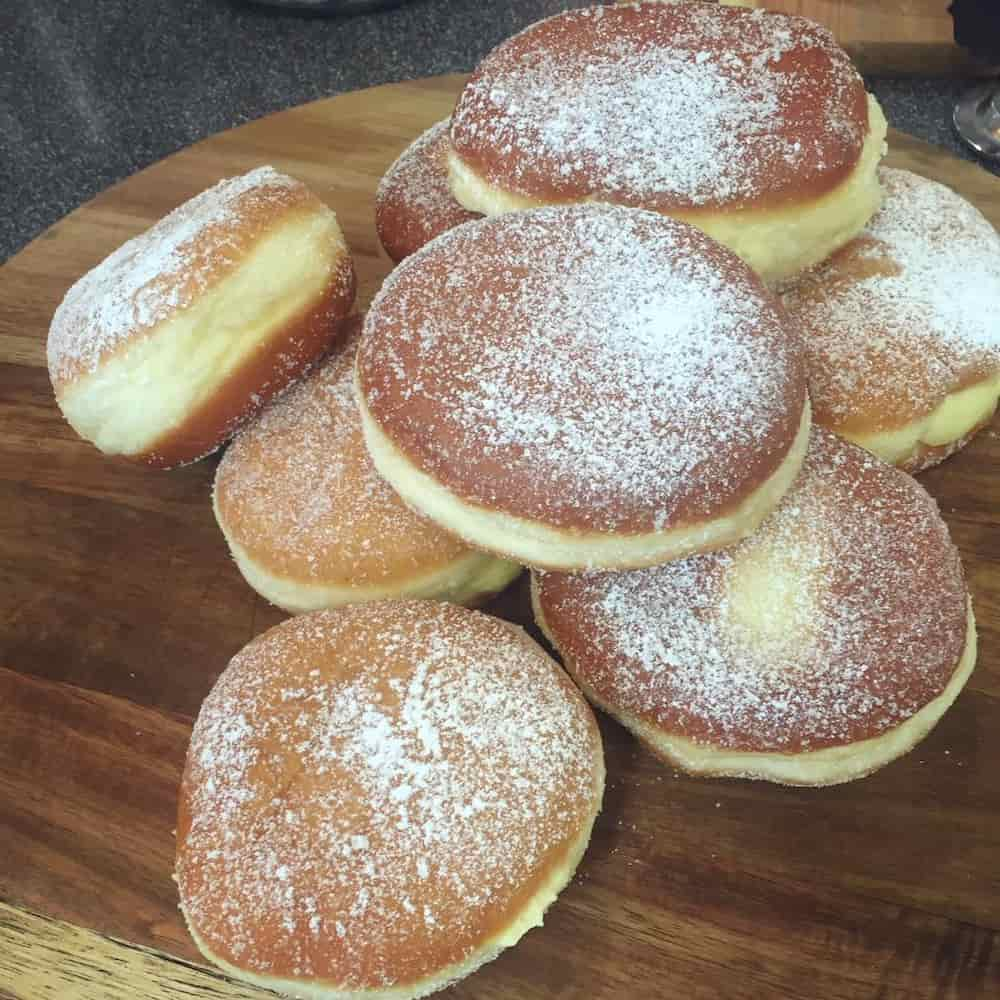 A pile of icing sugar coated Italian doughnuts - basically, without the hole!