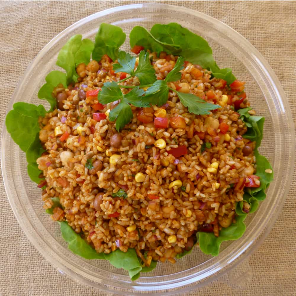 A bowl of cooked brown rice with chickpeas and corn on a bed of lettuce.