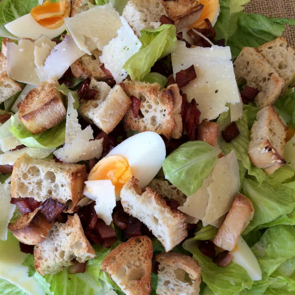 A bowl of lettuce, solf boiled eggs, bacon bits and croutons.
