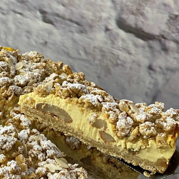 A slice of creamy cake with a crumbly topping.
