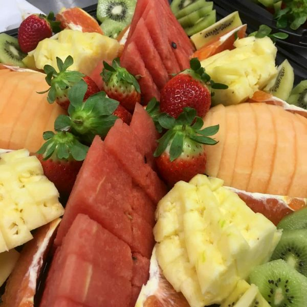 A platter of sliced water mellon, rock mellon, pineapple and strawberries.