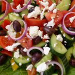 You are looking at a mix of cucumber, red onion, tomato, black olives and crumbled feta cheese.