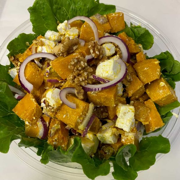 A bowl of roast pumpkin with red onion, walnuts and feta cheese on a bed of lettuce.