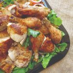 A platter of roasted pieces of chicken on a bed of fresh lettuce.