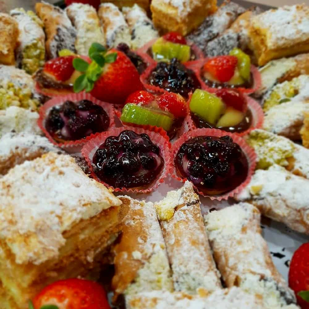A platter of icing sugar dusted pastries.