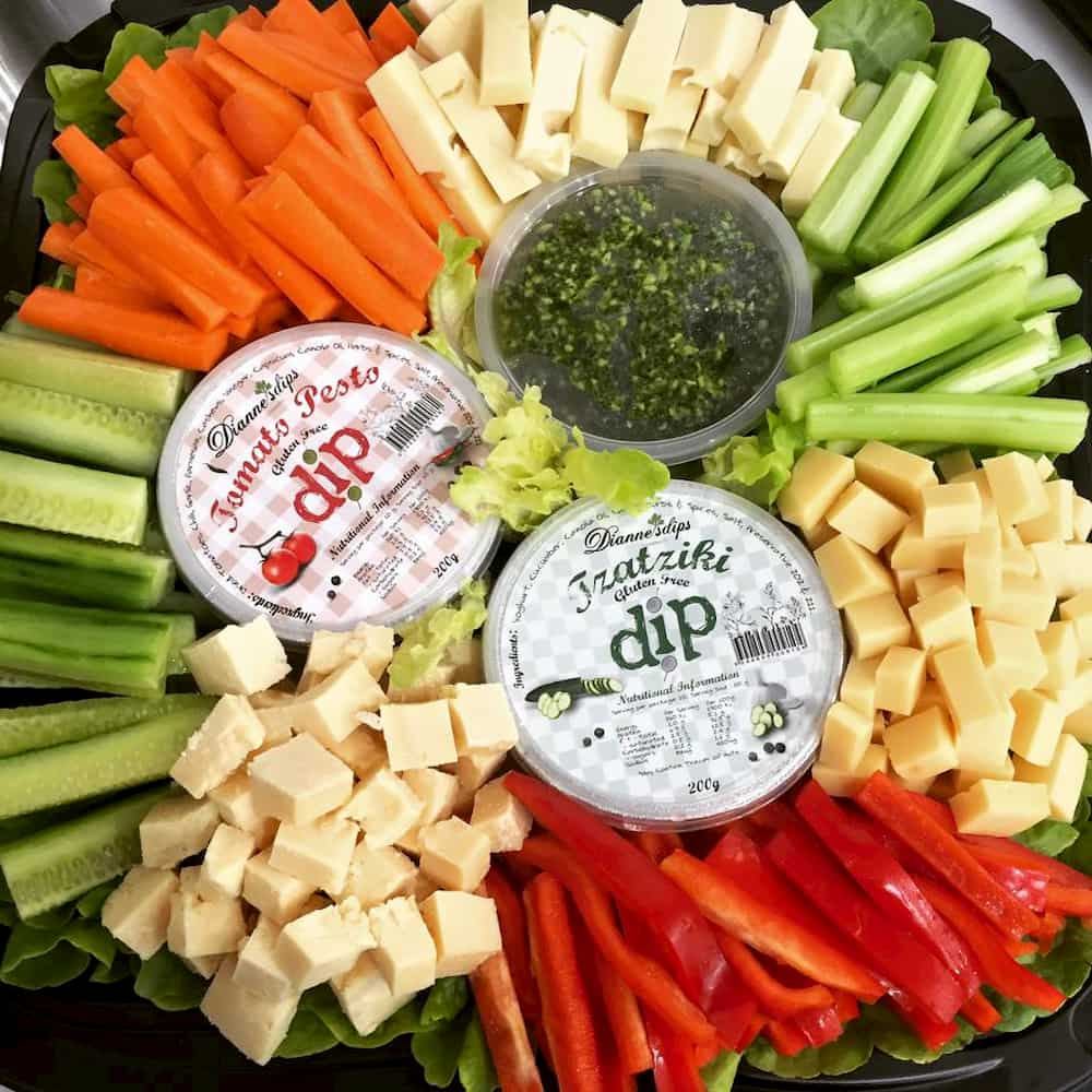 A colourful platter of vegetable sticks, cheeses and three containers of dips.
