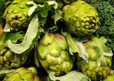 Fresh green artichokes stacked up on a shelf.