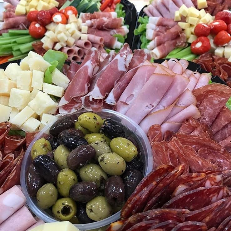Olives, slices of ham and cubes of cheese on a plate.