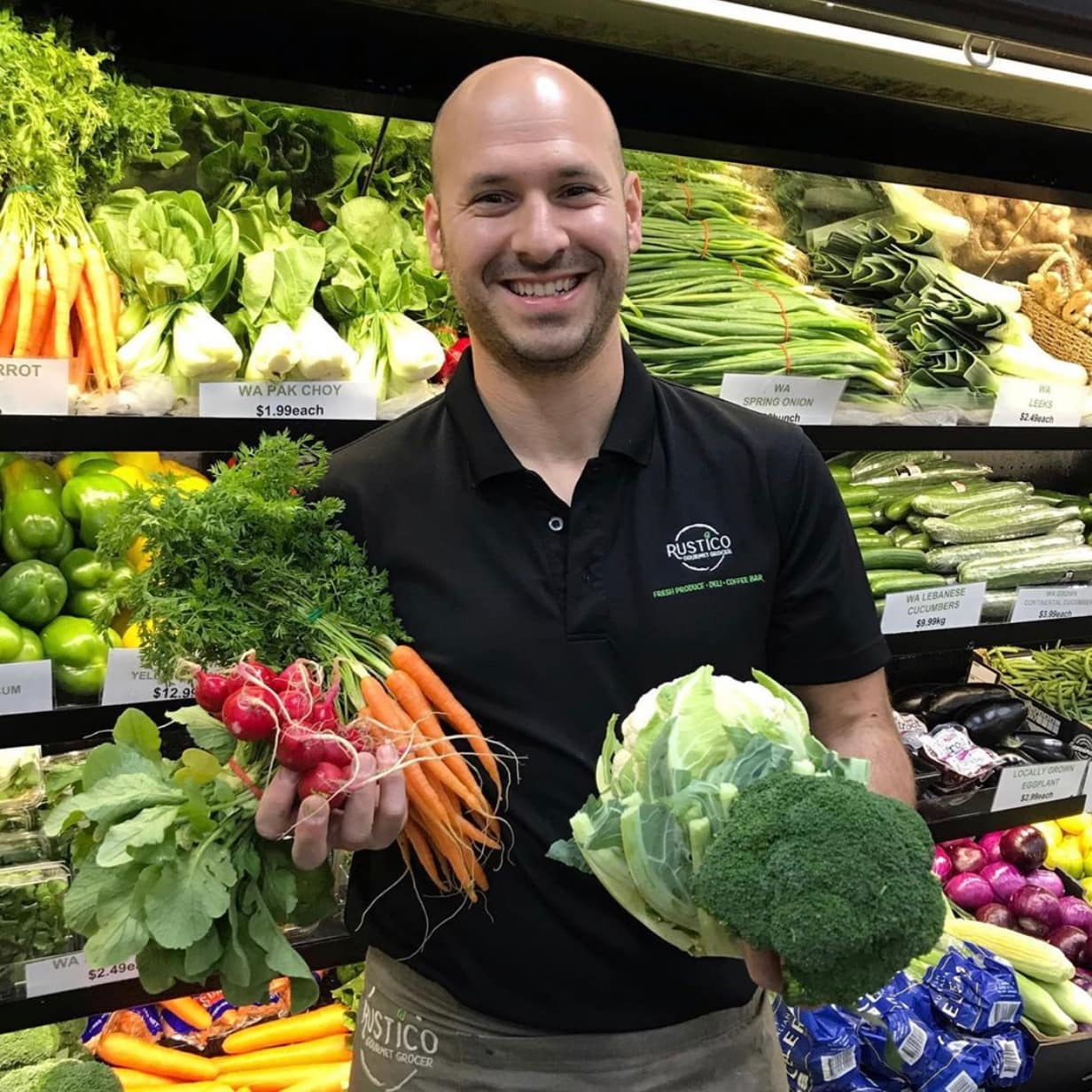 Rustico owner Giusep stands in front of the veggie cripers with carrots and broccoli in his hands.