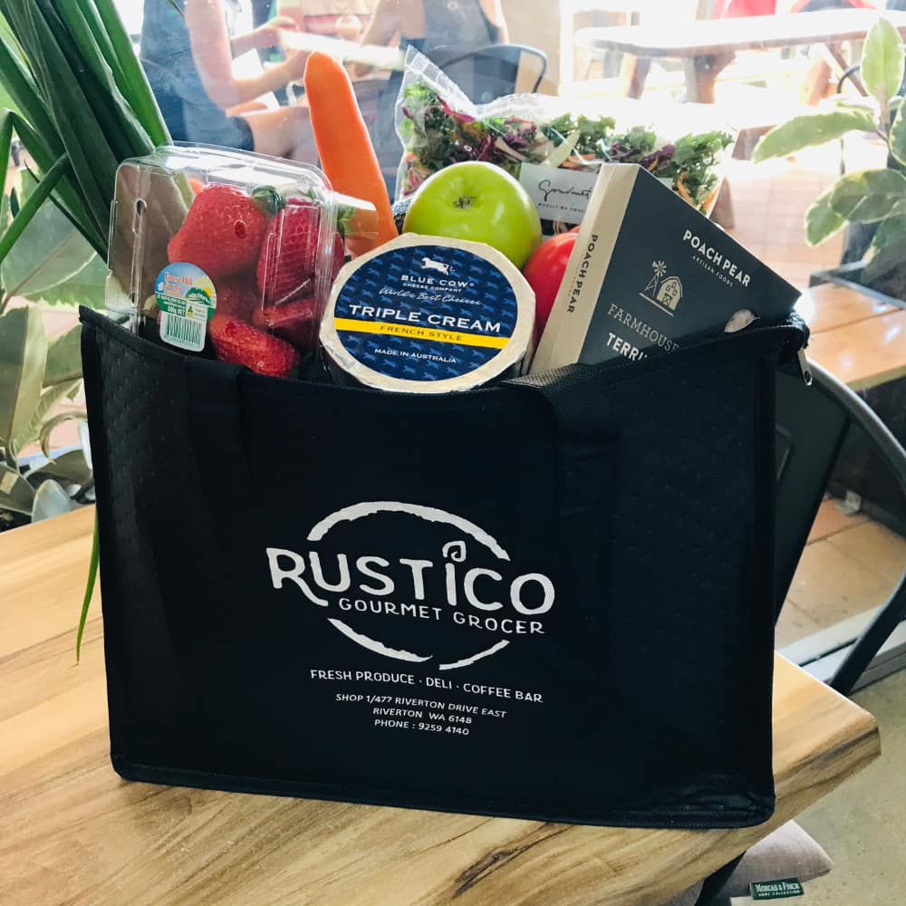 A Rustico shopping bag filled with groceries including cheese and vegetables.
