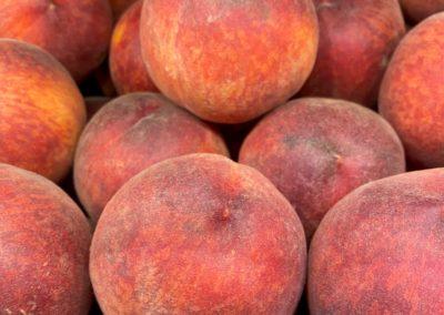 A dozen red and orange ripe peaches.