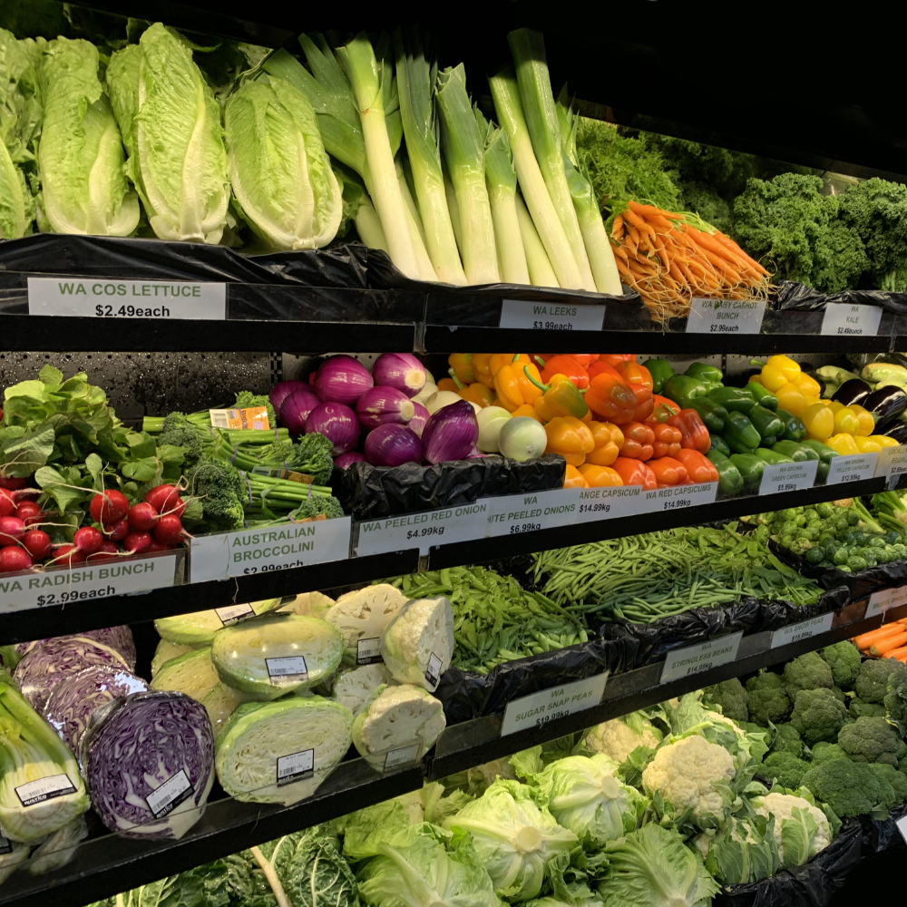 Shelves full of vegetables including leeks and lettuce and green beans.