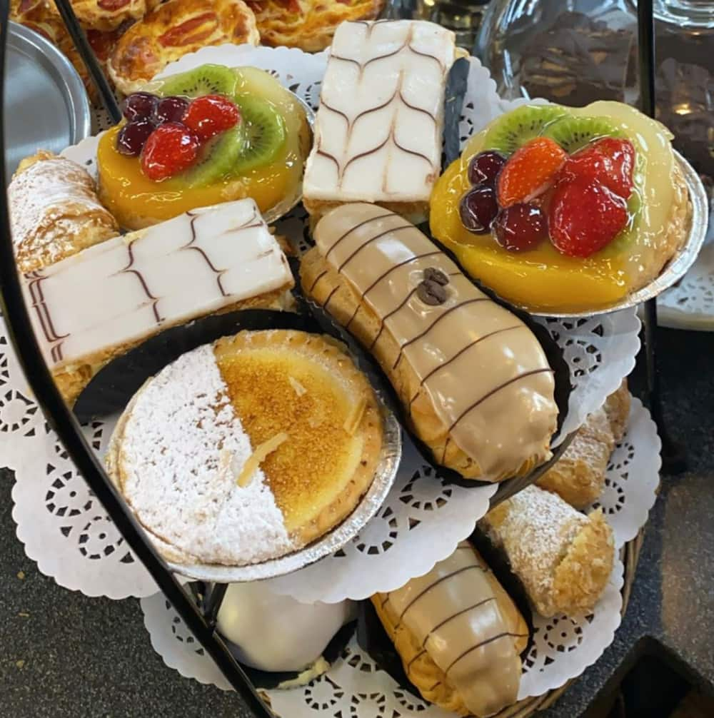 Two plates of Danishes and sweet pastries.
